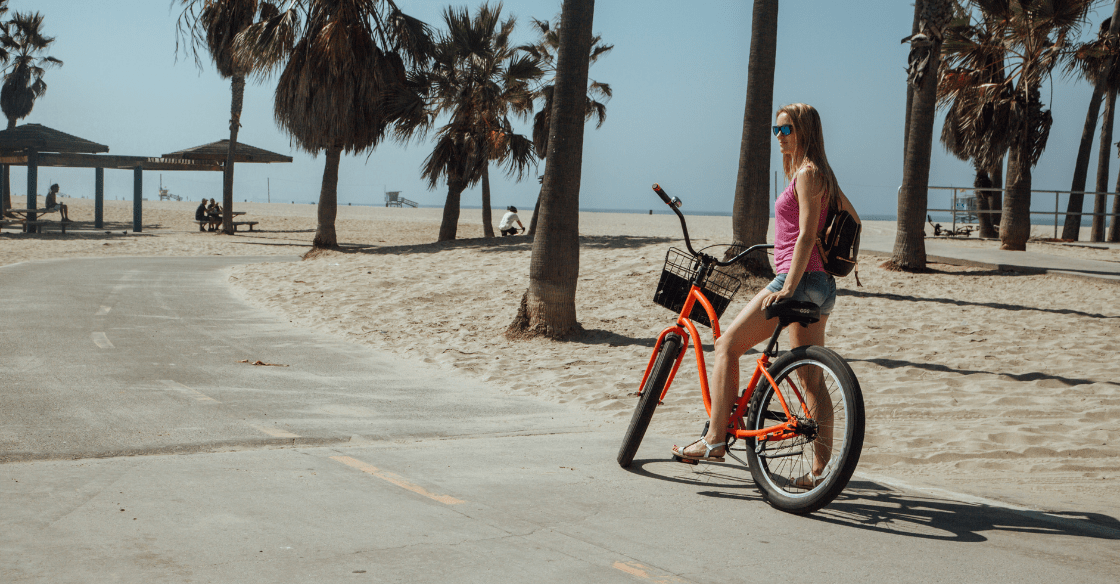 Girl riding a bike at the beach
